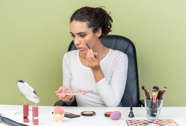 Młoda ładna kaukaska kobieta siedzi przy stole z narzędziami do makijażu, stosując cień do powiek i trzymając paletę cieni do powiek odizolowaną na oliwkowozielonej ścianie z miejsca na kopię