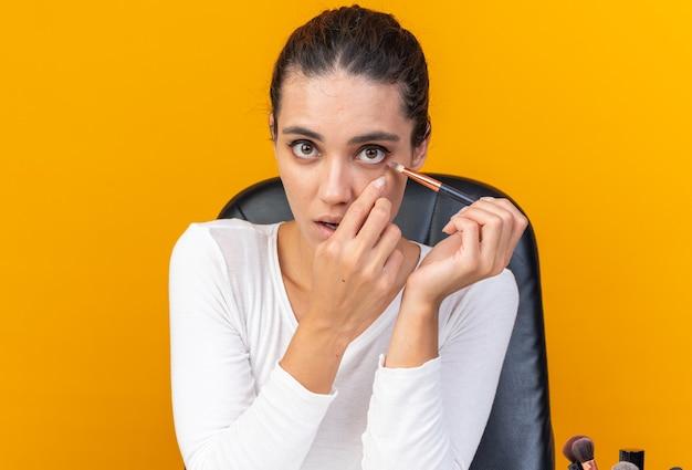 Młoda ładna kaukaska kobieta siedzi przy stole z narzędziami do makijażu, stosując cień do powiek za pomocą pędzla do makijażu na pomarańczowej ścianie z miejscem na kopię