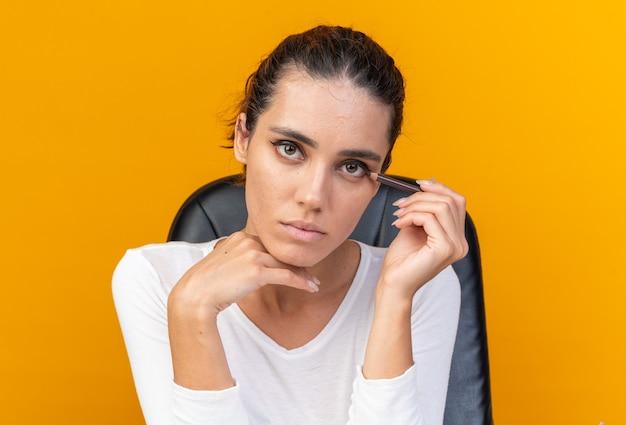 Młoda ładna kaukaska kobieta siedzi przy stole z narzędziami do makijażu, stosując eyeliner na pomarańczowej ścianie z miejscem na kopię
