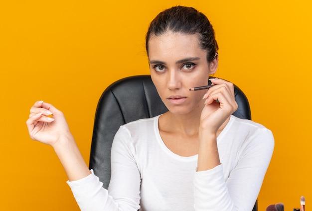 Młoda ładna kaukaska kobieta siedzi przy stole z narzędziami do makijażu, trzymając eyeliner na pomarańczowej ścianie z miejscem na kopię