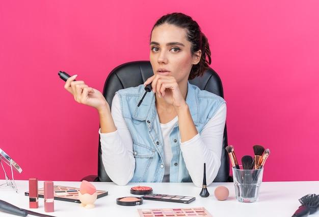 Młoda ładna kaukaska kobieta siedzi przy stole z narzędziami do makijażu, trzymając tusz do rzęs na różowej ścianie z miejscem na kopię