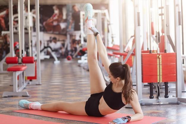 Młoda ładna kaukaska kobieta w sportswear pracującej z sprawności fizycznej stacją na ścianie out. zdrowa kobieta robi ćwiczenia rozciągające w klubie zdrowia, leżąc na macie jogi na podłodze.