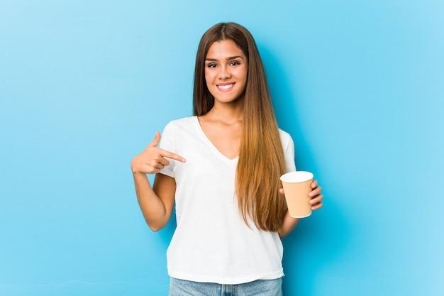 Młoda ładna kaukaski kobieta trzyma kawę na wynos osobę, wskazując ręką na przestrzeń kopii koszuli, dumny i pewny siebie