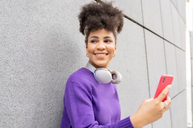 Młoda ładna kobieta, afro rasy mieszanej, na ulicy ze słuchawkami i smartfonem szczęśliwa, uśmiechnięta,