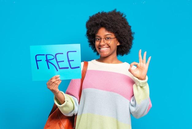 Młoda ładna kobieta afro trzymając darmową koncepcję transparent