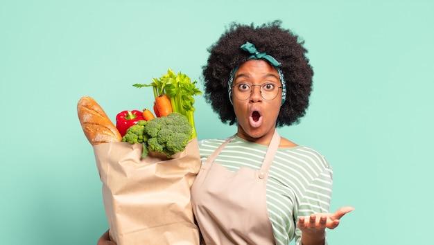 Młoda ładna kobieta afro z otwartymi ustami i zdumiona, zszokowana i zdumiona niesamowitą niespodzianką i trzymającą torbę z warzywami
