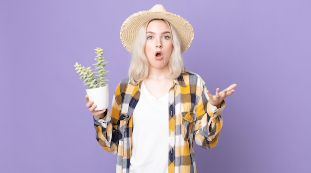 Młoda ładna kobieta albinos czuje się bardzo zszokowana i zaskoczona i trzyma kaktusa z rośliny doniczkowej