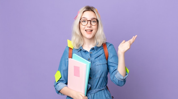Młoda ładna kobieta albinos czuje się szczęśliwa, zaskoczona, gdy zdaje sobie sprawę z rozwiązania lub pomysłu. koncepcja studenta