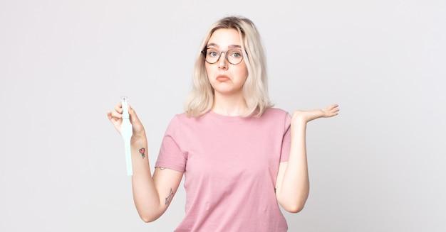 Młoda ładna kobieta albinos czuje się zakłopotana, zdezorientowana i wątpi, trzymając zegar w ręku