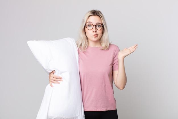 Młoda ładna kobieta albinos czuje się zakłopotana, zdezorientowana i wątpi w piżamę i trzyma poduszkę