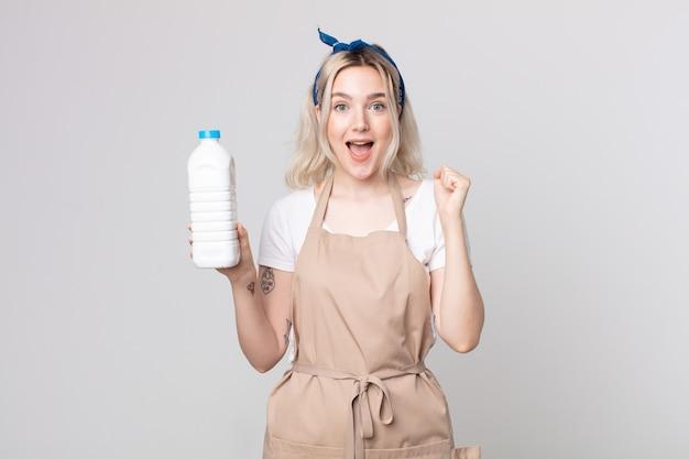 Młoda ładna kobieta albinos czuje się zszokowana, śmieje się i świętuje sukces butelką mleka