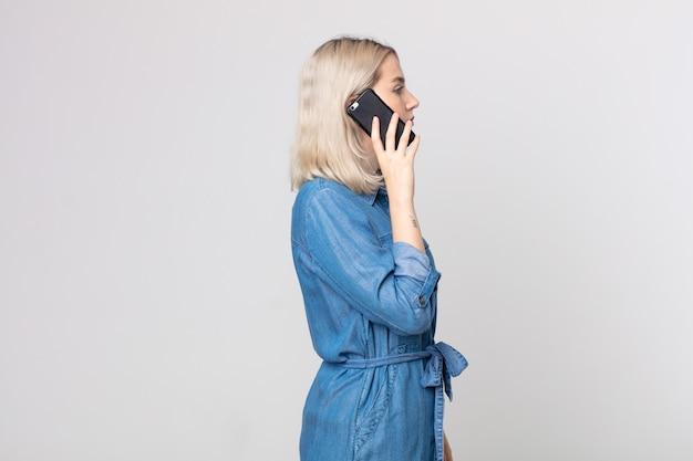 Młoda ładna kobieta albinos myśląca, wyobrażająca sobie lub marząca na jawie i rozmawiająca ze smartfonem w widoku profilu