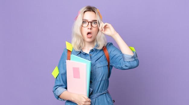 Młoda ładna kobieta albinos patrząc zdziwiona, realizując nową myśl, pomysł lub koncepcję. koncepcja studenta