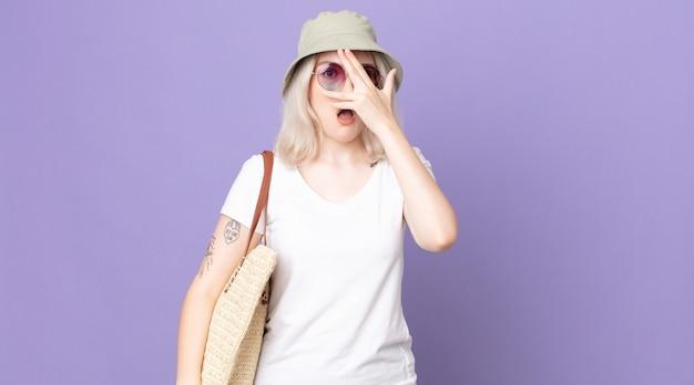 Młoda ładna kobieta albinos patrząc zszokowana, przestraszona lub przerażona, zakrywa twarz ręką. koncepcja lato