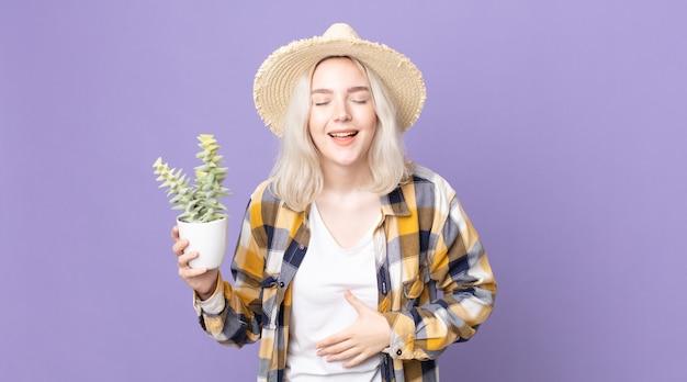Młoda, ładna kobieta albinos, śmiejąca się głośno z jakiegoś przezabawnego żartu i trzymająca kaktusa z rośliny doniczkowej