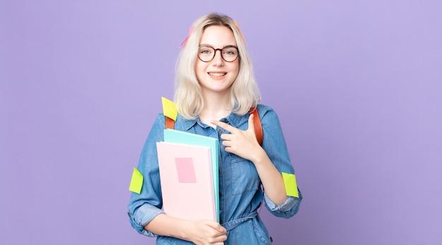 Młoda ładna kobieta albinos uśmiecha się radośnie, czuje się szczęśliwa i wskazuje na bok. koncepcja studenta