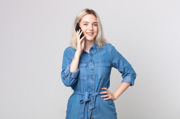 Młoda ładna kobieta albinos uśmiechająca się radośnie z ręką na biodrze, pewna siebie i rozmawiająca ze smartfonem