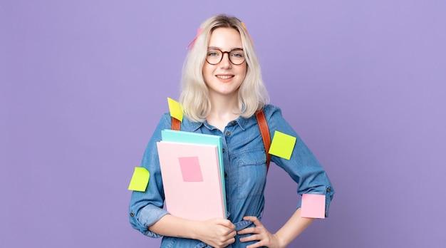 Młoda ładna kobieta albinos uśmiechający się szczęśliwie z ręką na biodrze i pewny siebie. koncepcja studenta