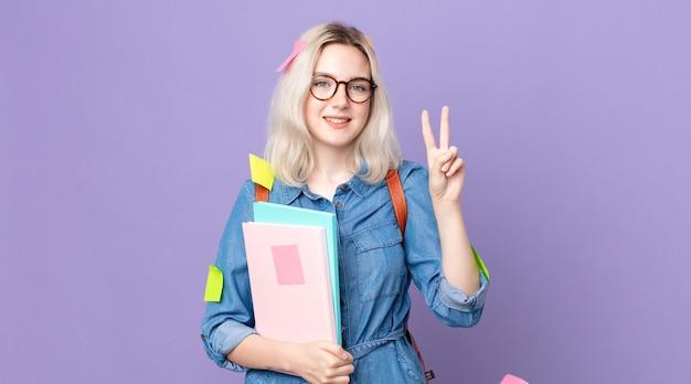 Młoda ładna kobieta albinos uśmiechnięta i patrząca przyjaźnie, pokazująca numer dwa. koncepcja studenta