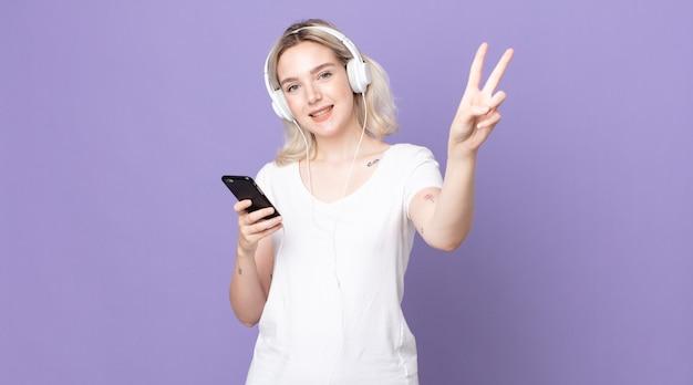 Młoda ładna kobieta albinos uśmiechnięta i wyglądająca na szczęśliwą, gestykulująca zwycięstwo lub pokój za pomocą słuchawek i smartfona