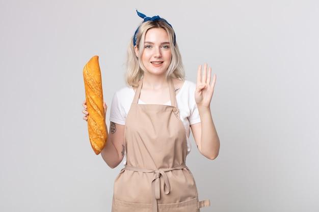 Młoda ładna kobieta albinos uśmiechnięta i wyglądająca przyjaźnie, pokazująca numer cztery z bagietką chlebową