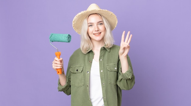 Młoda ładna kobieta albinos uśmiechnięta i wyglądająca przyjaźnie, pokazująca numer trzy i trzymająca wałek do malowania