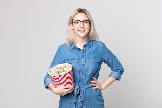 Młoda ładna kobieta albinos uśmiechnięta radośnie z ręką na biodrze i pewna siebie z wiadrem popcorns