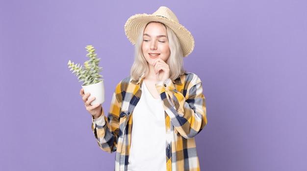 Młoda ładna kobieta albinos uśmiechnięta ze szczęśliwym, pewnym siebie wyrazem twarzy z ręką na brodzie i trzymająca kaktusa z rośliny doniczkowej