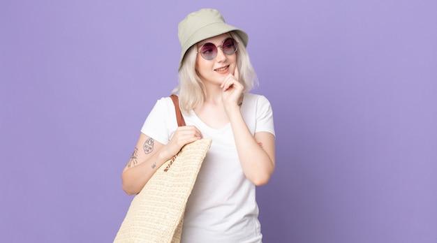 Młoda ładna kobieta albinos uśmiechnięta ze szczęśliwym, pewnym siebie wyrazem z ręką na brodzie. koncepcja lato