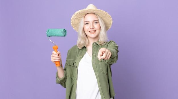 Młoda ładna kobieta albinos wskazująca na kamerę, wybierająca cię i trzymająca wałek do malowania