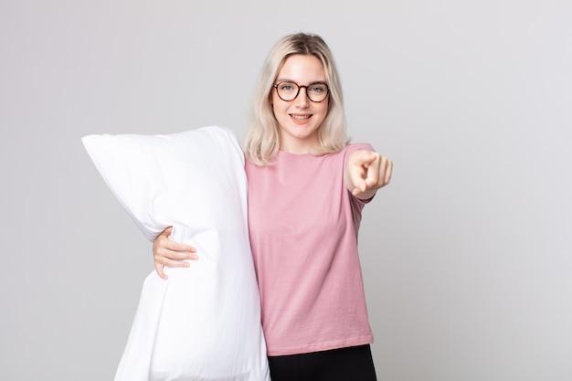 Młoda ładna kobieta albinos wskazująca na kamerę, wybierająca cię w piżamie i trzymającą poduszkę