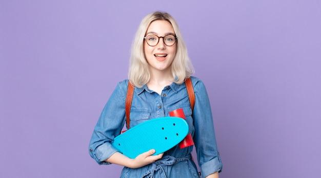 Młoda ładna kobieta albinos wygląda na szczęśliwą i mile zaskoczoną i trzyma deskorolkę