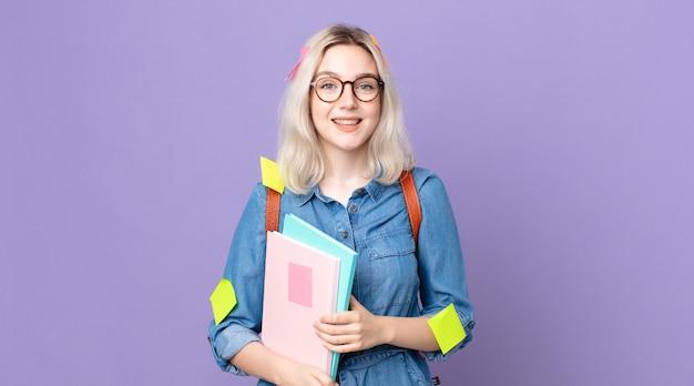 Młoda ładna kobieta albinos wygląda na szczęśliwą i mile zaskoczoną. koncepcja studenta