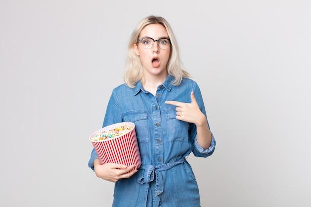 Młoda ładna kobieta albinos wygląda na zszokowaną i zaskoczoną z szeroko otwartymi ustami, wskazując na siebie wiadrem z popcornem