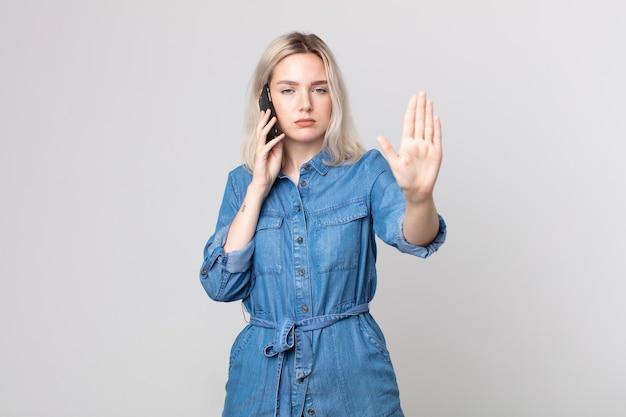 Młoda ładna kobieta albinos wygląda poważnie pokazując otwartą dłoń, wykonując gest zatrzymania i rozmawiając ze smartfonem
