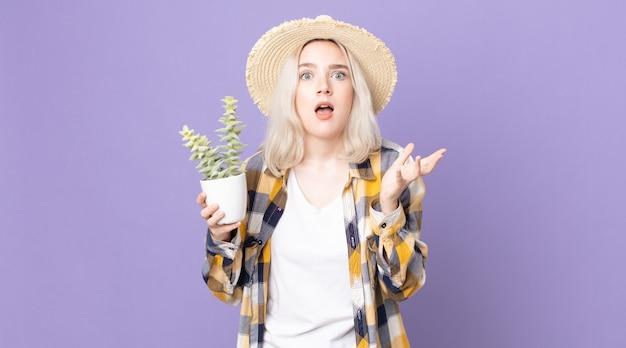 Młoda ładna kobieta albinos wyglądająca na zdesperowaną, sfrustrowaną i zestresowaną, trzymająca kaktusa z roślin doniczkowych