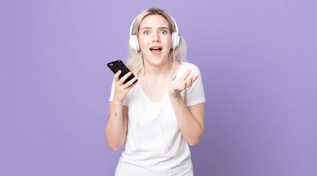 Młoda, ładna kobieta albinos wyglądająca na zdesperowaną, sfrustrowaną i zestresowaną ze słuchawkami i smartfonem
