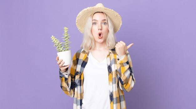 Młoda, ładna kobieta albinos wyglądająca na zdziwioną z niedowierzaniem i trzymająca kaktusa z rośliny doniczkowej