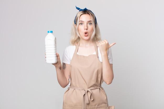 Młoda ładna kobieta albinos wyglądająca na zdziwioną z niedowierzaniem z butelką mleka