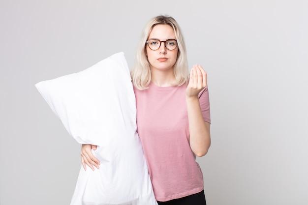 Młoda ładna kobieta albinos wykonująca gest kaprysu lub pieniędzy, mówiąca, żebyś zapłaciła, mając na sobie piżamę i trzymając poduszkę
