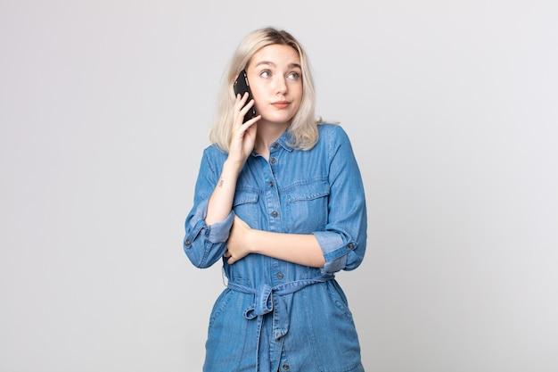 Młoda ładna kobieta albinos wzrusza ramionami, czuje się zdezorientowana i niepewna i rozmawia ze smartfonem