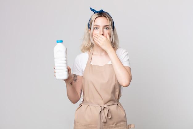 Młoda ładna kobieta albinos zakrywająca usta rękami zszokowana butelką mleka