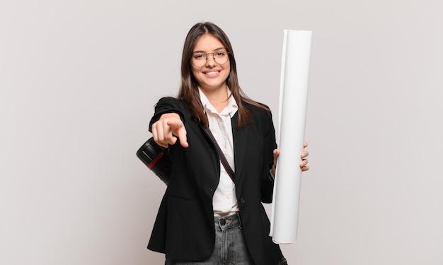 Młoda ładna kobieta architekta wskazująca na aparat z zadowolonym, pewnym siebie, przyjaznym uśmiechem, wybierająca ciebie