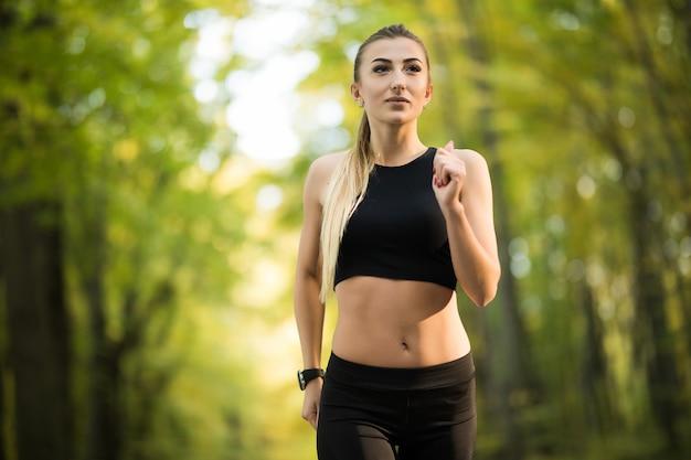 Młoda ładna kobieta biega w parku latem