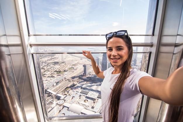 Młoda ładna kobieta bierze selfie na szczycie burj khalifa