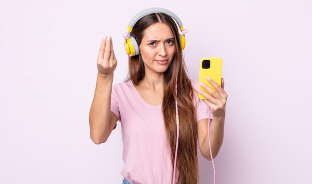 Młoda ładna kobieta co capice lub pieniądze gest, mówiąc, aby zapłacić. słuchawki i smartfon