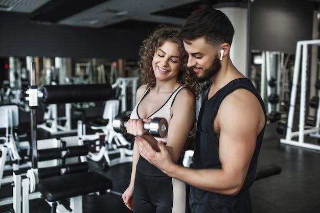 Młoda ładna kobieta ćwiczy na siłowni, robi loki na biceps z pomocą swojego osobistego trenera