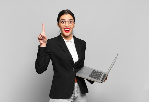 Młoda ładna kobieta czując się jak szczęśliwy i podekscytowany geniusz po zrealizowaniu pomysłu, radośnie podnosząc palec, eureka!. koncepcja laptopa