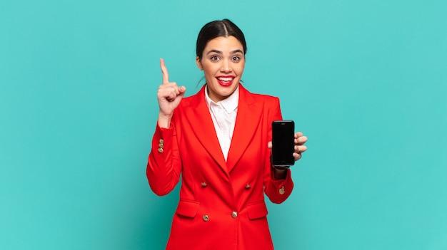 Młoda ładna kobieta czująca się jak szczęśliwa i podekscytowana geniusz po zrealizowaniu pomysłu, radośnie podnosząca palec, eureka!