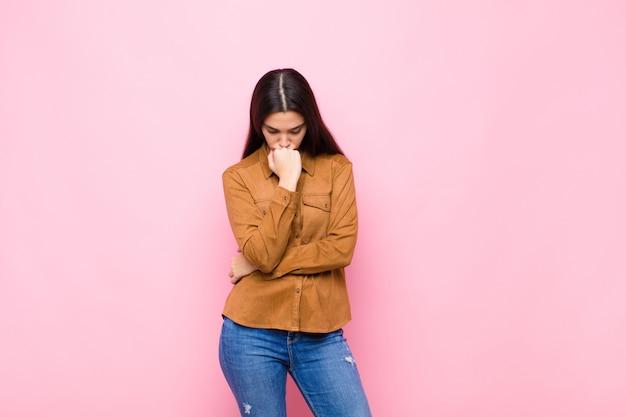 Młoda ładna kobieta czująca się poważnie, zamyślona i zatroskana, wpatrująca się w bok ręką przyciśniętą do brody na różowej ścianie